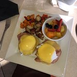 Eggs Benedict, hash browns and fruit