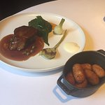 Main dish of mouth watering lamb, seared onion, purée asparagus and roasted potatoes.