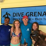Some of the staff with myself and my friend in front of the Dive Grenada sign!