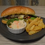 Beef-burger with cheese and fresh salad in a long bun, served with fries and coleslaw