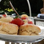 Afternoon tea top layer - fruit scones with fresh strawberries and pots of cream desert