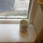Dirty mug on the windowsill right outside the creaky lift!