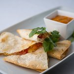 Porkadilla- a quesadilla with two cheeses, pickled onions and braised pork with our roasty salsa