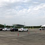 a row of CTS-Vs with the Arlington Park Racecourse grandstands in the background