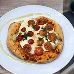 Pizza individual con queso brie, tomates cherry, albahaca y oliva.