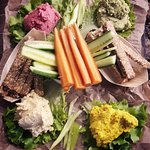 4 types of humus servings, carrot sticks, cucumber and pepper sticks and wholegrain sticks