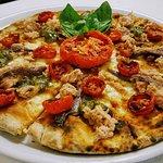 Pizza con mozzarella, pomodorini confit e pesto di pistacchi