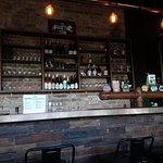Daytime photo of the bar - copper bench, heavy duty pipes, wood front, select alcohols.