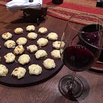 more appetisers of melted cheese and sausages cooked in red wine