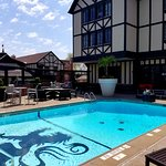 Photo of the pool shows the hotel's Tudor-style exterior.