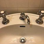 Broken faucet. Leaking cold water handle on left.