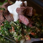Top Sirloin Steak over Tabbouleh salad and topped with homemade Tzatziki