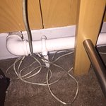 Disgusting scene between bedside table and bed - that cable was actually WHITE once