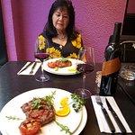 Mijn vrouw kijkt verheeerlijkt naar het versierde bord met de rib eye en gepofte tomaat
