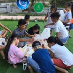 Kids with parents decorating kites