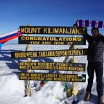 """Climb Kili: At the summit with our guides: """"Good Luck"""" and Armani."""
