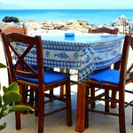 Tables by the road and the rocky shore