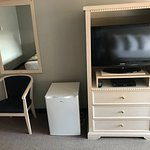 left to right: comfy chair, second fridge in room; dresser and flatscreen TV