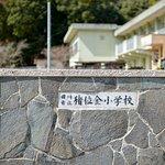 正門右側には旧「猪位金小学校」の銘板。