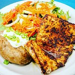 Blackened Mahi mahi served with a baked potato with sour cream and chives and garden salad