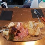 Mixed meat & cheese board with pickles and breads.