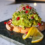 An extremely yummy avocado-toast with pomegranate sitting on a nice looking platter.