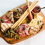 Cured meat board with aged cheddar, olives & seeded baguette from The Gold Bar Snack Menu