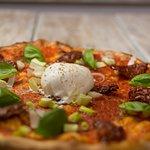 La pizza Gustosa, con Passata di pomodoro, Pomodorini secchi, Cipollotto fresco, Basilico e Burr