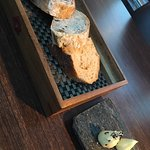 Various Breads: white sourdough, cranberry and fennel seed bread, mixed olive bread with butter