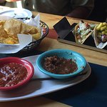 2 flavors of salsa with chips, Strawberry Margarita in front right