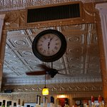 Old clock in front of mirror over the bar