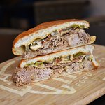 Sandwich Cubano Piccante with mojo pulled pork, jalapeños, cheese, bacon, mustard and chipotle m