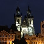 Sculpture of Jan Huss and the Tyn Church in the background, at night in the old town Prague