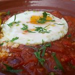 A cuisine of egg, peppers, and tomatos.