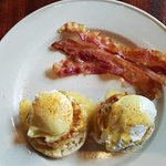 Eggs on English muffins relaxing on a crabcake bed and crispy bacon