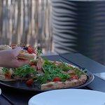 Pizza z mozzarellą, szynką, czarnymi oliwkami, rukolą i pomidorkami koktajlowymi