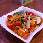 Spicy tender chicken curry with spring vegetables served on noodles.