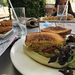 Fried Green Tomato sandwich with chicken fingers in the background