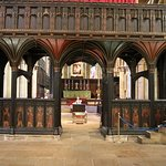 Painted choir screen with Frith chair beyond
