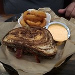 Burger on rye bread with bacon and onion rings on the side.