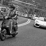 Lady on a scooter vs a chap in a Lamborghini, Garden Road, Hong Kong