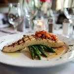 Grilled swordfish served with asparagus and topped with bruschetta in scampi sauce.