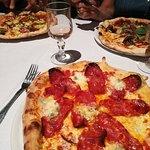 Pizza Diavola en premier plan (tomate - mozzarella - gorgonzola - sorte de chorizo italien)