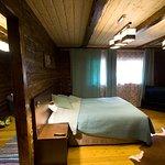 Маленькая темная комната с низкими потолками и преимущественно голыми стенами.