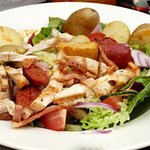 succulent grilled chicken strips on salad with potatoes