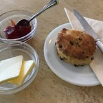 Home baked scone served with butter and strawberry jam.