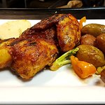 Oven roasted half chicken marinated in a herb and garlic rub, served with roasted potatoes and v