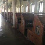 Las hileras de pupitres y bancos, bajo arcadas, y con el escudo de Malatesta en los lados