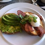 Avocado, bacon and poached egg on a bagel