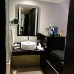 superior class room - bathroom basin in main room with mini bar and luggage on right